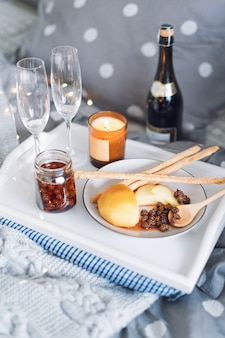 Breakfast in bed, a tray with cheese, grissini, jam from young fir cones, champagne and a candle