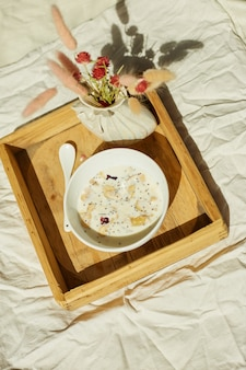 Breakfast in bed, try with bowl muesli, granola and flower in sunlight at home, chambermaid bringing tray with breakfast in hotel room, good service