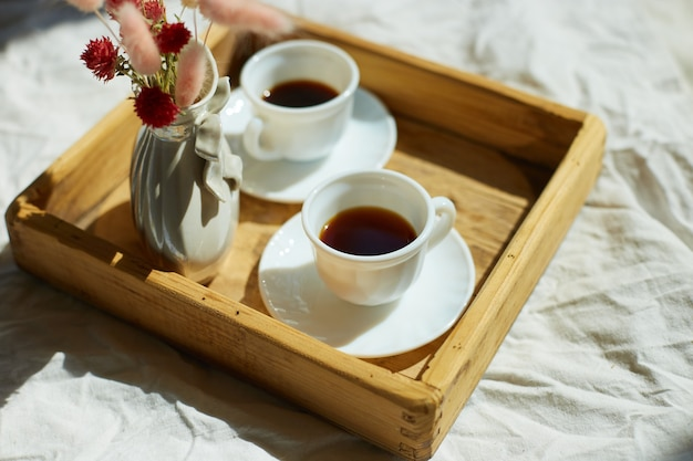 Breakfast in bed, try with two cups coffee and flower in sunlight at home, chambermaid bringing tray with breakfast in hotel room, good service