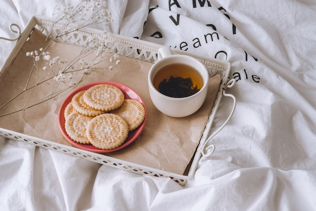 Breakfast in bed. white bed, a tray with tea and cookies. morning at home