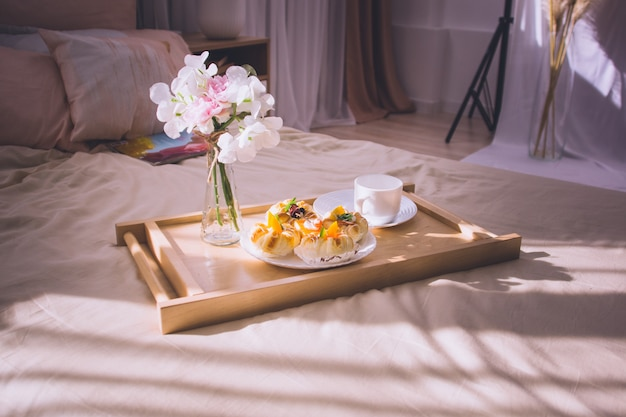 Breakfast in bed with coffee, buns, flowers on wooden tray in hotel bed or at home. window light