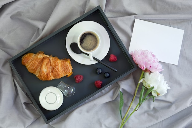 Breakfast in bed with coffee, croissant and milk