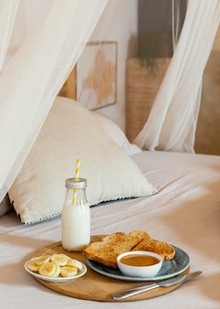 Breakfast in bed with milk, banana and bread