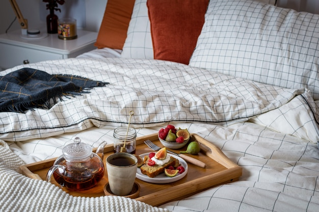 Breakfast in bed with pastry and fresh fruits, black tea