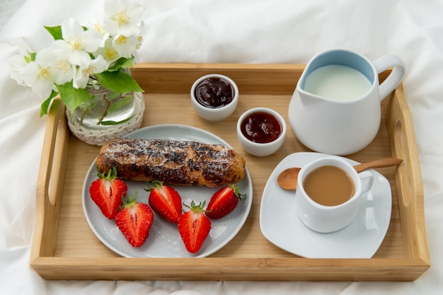Breakfast in bed. wooden tray with coffee, jam, strawberries and eclair . jewelry with delicate white flowers.
