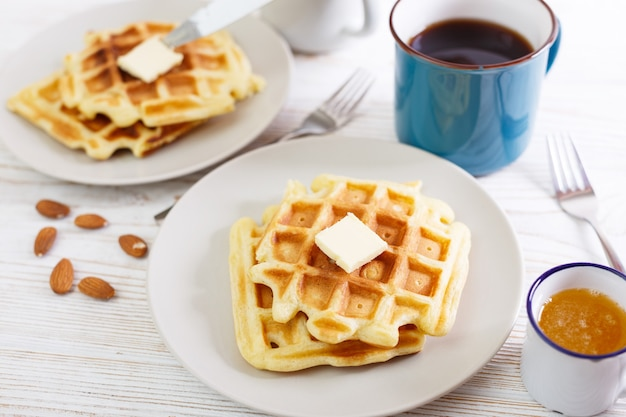 Breakfast - belgian waffles with honey and cup with tea