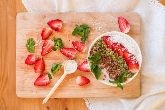 Чаша для смузи с ягодами на завтрак, посыпанная клубникой, тыквенными семечками, кокосовыми мюсли и свежей мятой