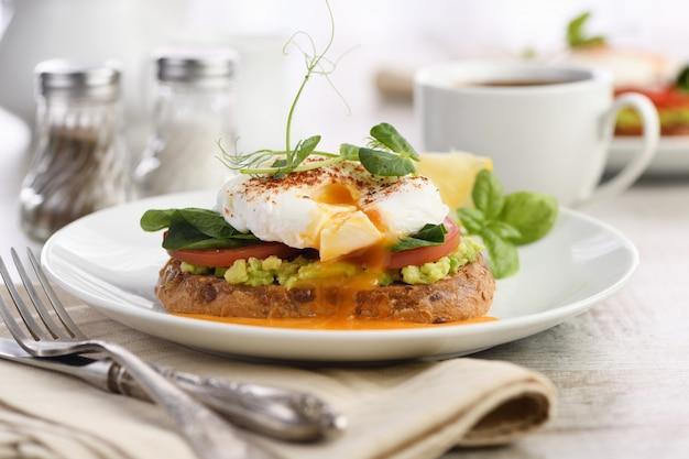 朝ごはん。ワカモレとほうれん草のシリアルトーストにスライスしたベストエッグベネディクト