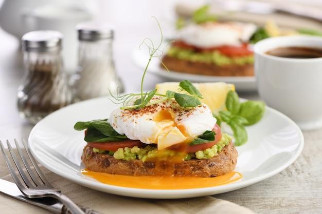 Завтрак. best eggs benedict на ломтике поджаренного зернового хлеба с гуакамоле и шпинатом