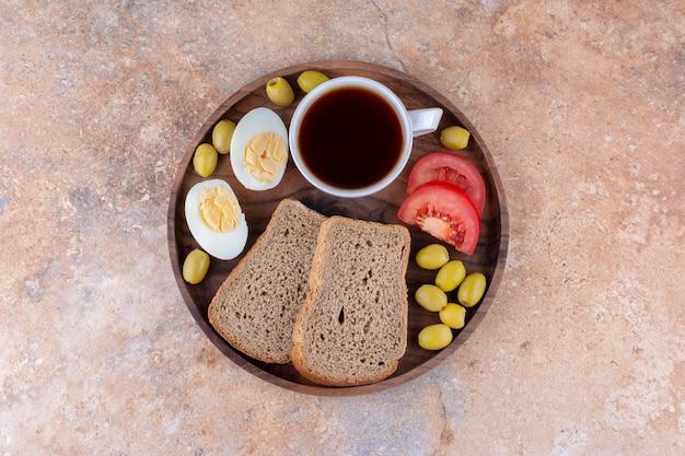 Tagliere per la colazione con fette di pane, verdure e una tazza di tè