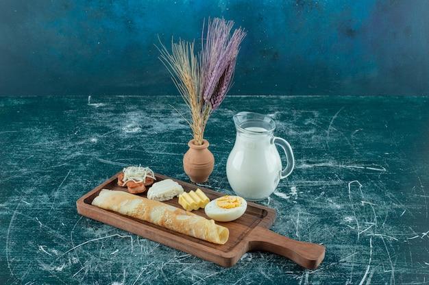 Tagliere colazione con crepes e un vasetto di latte. foto di alta qualità
