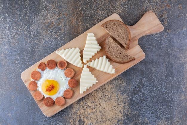 Tagliere colazione con uova, salsiccia e pane