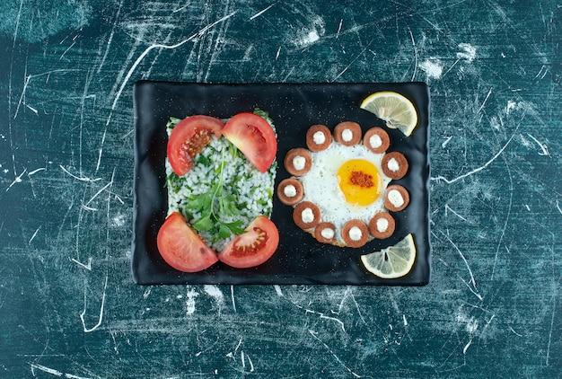 Tagliere per la colazione con uova fritte e insalata. foto di alta qualità