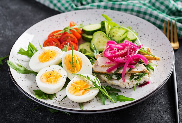 Breakfast. boiled eggs salad with greens, cucumbers, tomato and sandwich with ricotta cheese, fried chicken fillet and red onion. keto/paleo lunch.