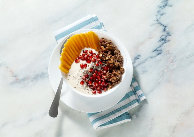 Breakfast bowl of granola, yogurt, fresh sweet mango, chia seeds, pomegranate seeds and maple syrup on a blue striped napkin