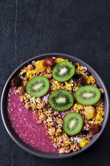 Breakfast bowl with acai smoothie, oatmeal, granola and fruit.