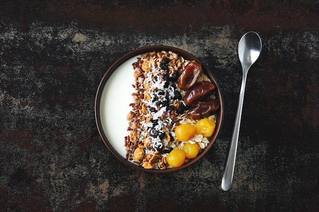Breakfast bowl with greek yogurt, oatmeal, granola and dried fruit.