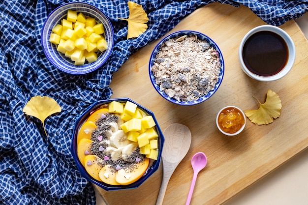 Breakfast bowl with oat, yogurt, mango, persimmon and chia, top view