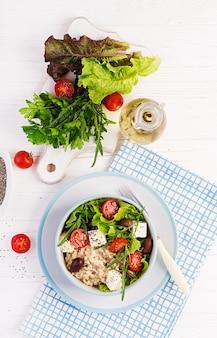 Чаша для завтрака с овсянкой, помидорами, сыром, листьями салата и оливками