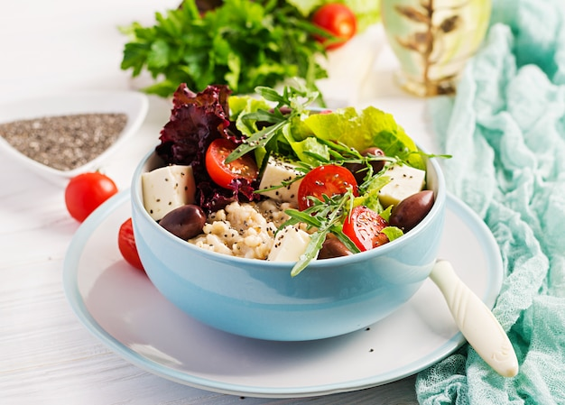 Breakfast bowl with oatmeal, tomatoes, cheese, lettuce and olives. healthy food. vegetarian buddha bowl.