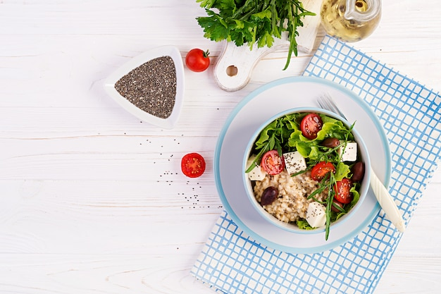 Breakfast bowl with oatmeal, tomatoes, cheese, lettuce and olives. healthy food. vegetarian buddha bowl
