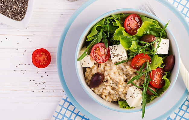 Breakfast bowl with oatmeal, tomatoes, cheese, lettuce, and olives