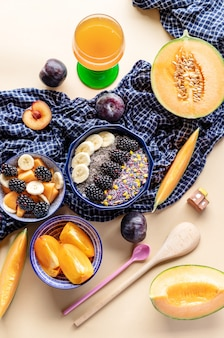 Breakfast bowl with oatmeal, yogurt, blackberries, persimmon, melon and chia seeds, top view