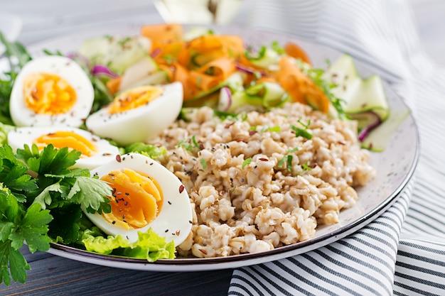 Чаша для завтрака с овсяной кашей, цуккини, листьями салата, морковью и вареным яйцом