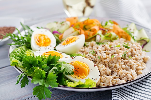 Breakfast bowl with oatmeal, zucchini, lettuce, carrot and boiled egg