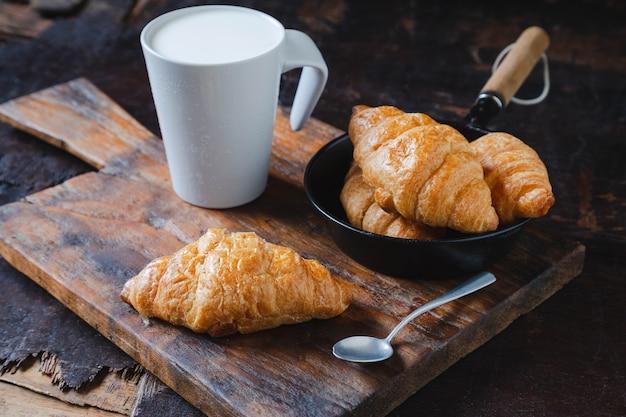 Хлеб для завтрака, круассаны и свежее молоко на деревянном столе.