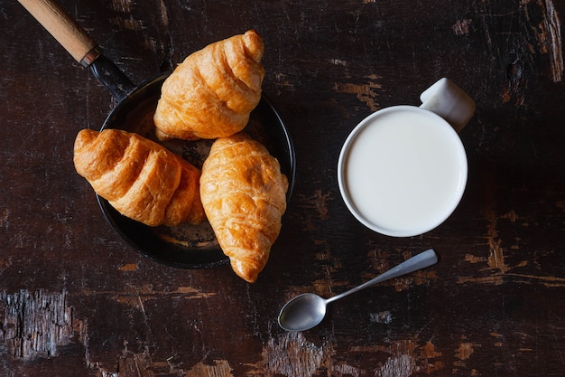 Breakfast bread, croissants and fresh milk on the wooden table.