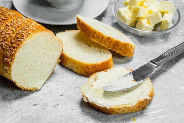 아침밥. 버터와 뜨거운 커피를 곁들인 빵. 소박한 테이블에.