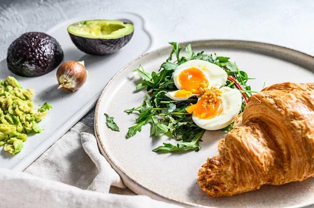 Завтрак, поздний завтрак с авокадо, рукколой, круассаном и яйцом. серый фон вид сверху