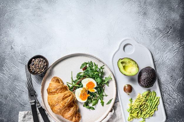 아침, 아보카도, arugula, 크로와상 계란 브런치. 회색 배경. 평면도. 텍스트를위한 공간
