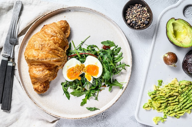 Завтрак, бранч с авокадо, рукколой, круассаном и яйцом