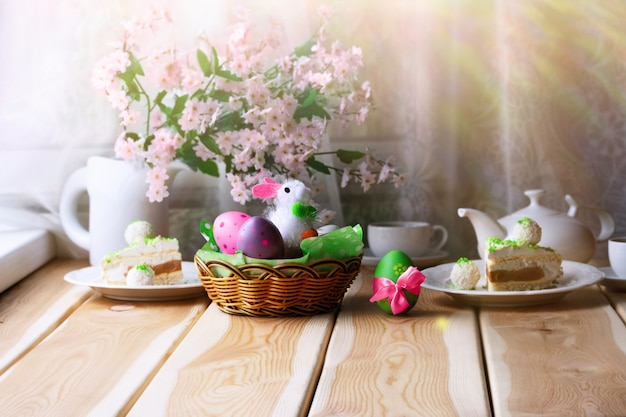 Breakfast or brunch on wooden  table with easter  bunny, colored eggs,  easter pastry and cup of tea. easter morning consept.