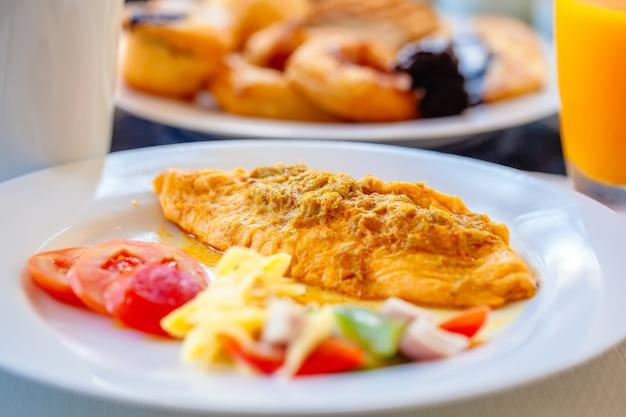 ラグジュアリーホテル、オムレツ、野菜と新鮮なパン、クロワッサンでの朝食ビュッフェ。おいしい料理のプレートが付いているダイニングテーブル。食べ物のプレート、ガラスとコーヒーカップのオレンジジュースとホテルの食べ物
