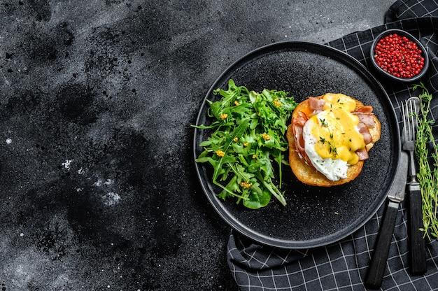 Breakfast burger with bacon, egg benedict, hollandaise sauce on brioche bun.