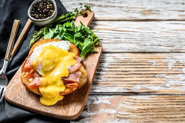 Завтрак бургер с беконом, яйцом бенедикт, голландским соусом на булочке. украсить салатом из рукколы. белый фон.