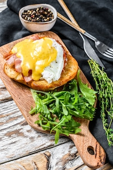 ベーコン、エッグベネディクト、ブリオッシュパンにオランデーズソースを添えた朝食バーガー。ルッコラのサラダを飾る。