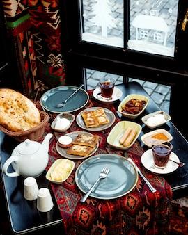 焼きたてのパンのオムレツとバターとチーズを窓際で朝食