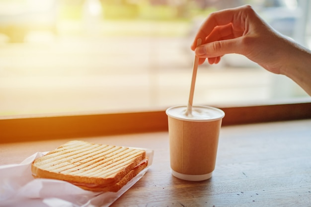 Breakfast in cafe with coffee and toast. woman's hand stirs coffee in paper cup