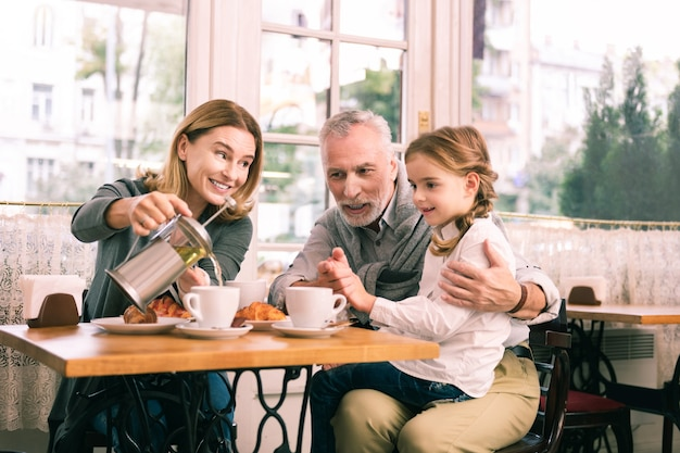 Breakfast in cafeteria. happy grandparents and cute little girl feeling memorable while having breakfast in cafeteria