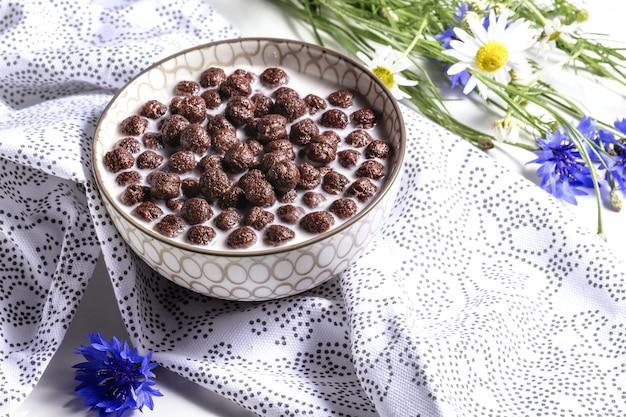 朝食用シリアル、ミルクのチョコレートシリアル、コーンフラワーナチュラルナプキンに花、ソフトフォーカスの子供のための健康的な栄養の概念。