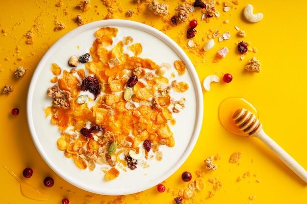 Хлопья для завтрака кукурузные хлопья, орехи, семена, ягоды и мед в миске с молоком