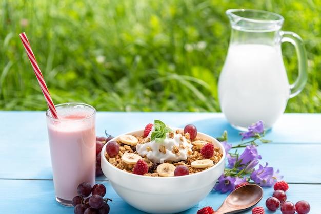우유와 라스베리, 포도, 바나나와 밝은 파란색 표면에 짚으로 베리 요구르트 한 잔과 함께 아침 시리얼. 공간을 복사하십시오.