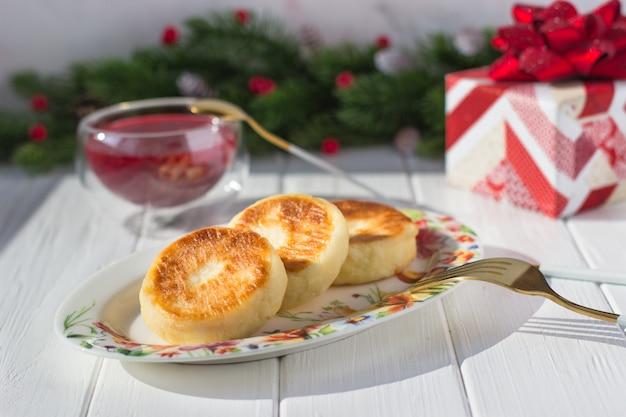コーンと赤いベリーとギフトとモミの枝の背景に朝食チーズのパンケーキとラズベリージャム