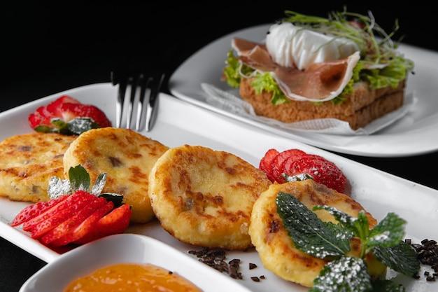 Завтрак. чизкейки с тостами на белой тарелке на черной поверхности