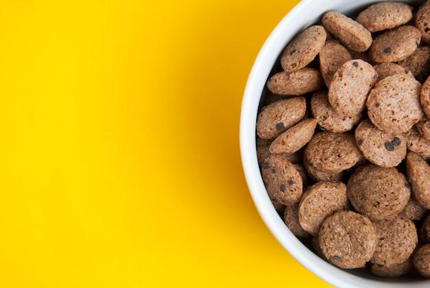 노란색 배경에 아침 초콜릿 알 약입니다.