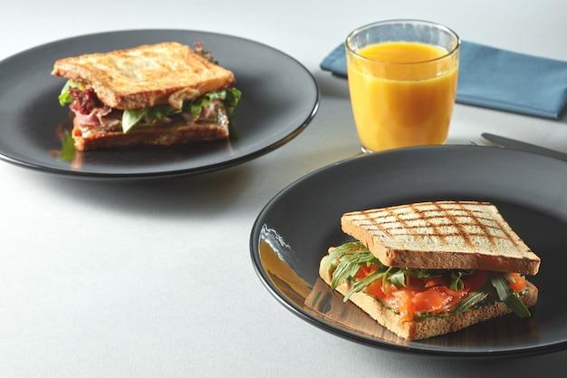 テーブルの上にオレンジジュースと朝食クラブサンドイッチ